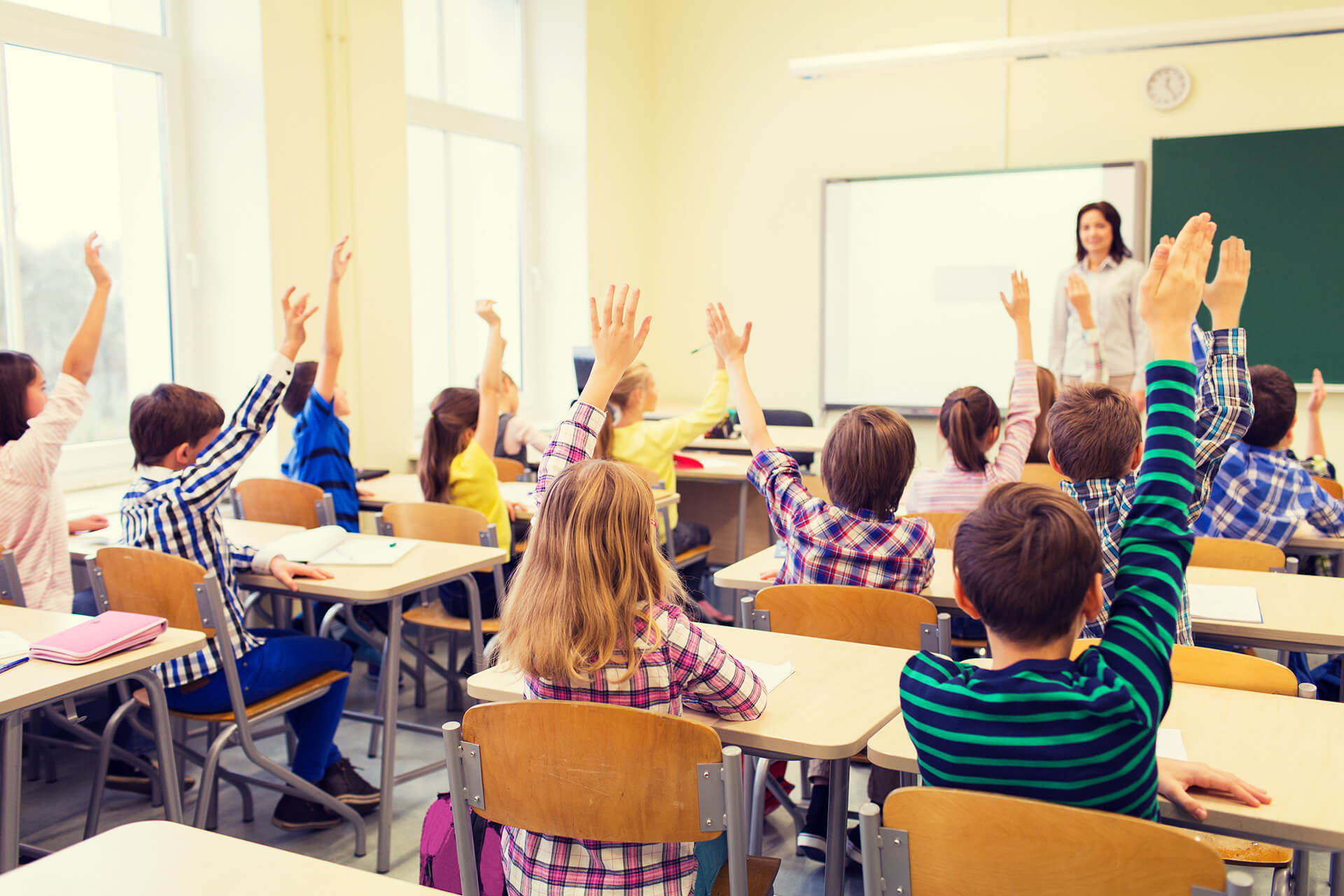 Elementary students raising hand in class.
