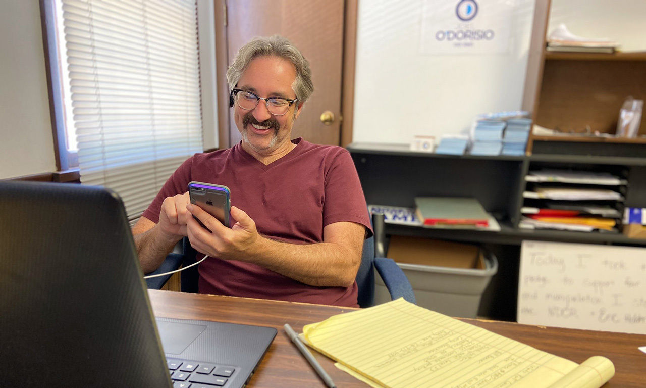 Joel smiling while looking at phone in campaign office.