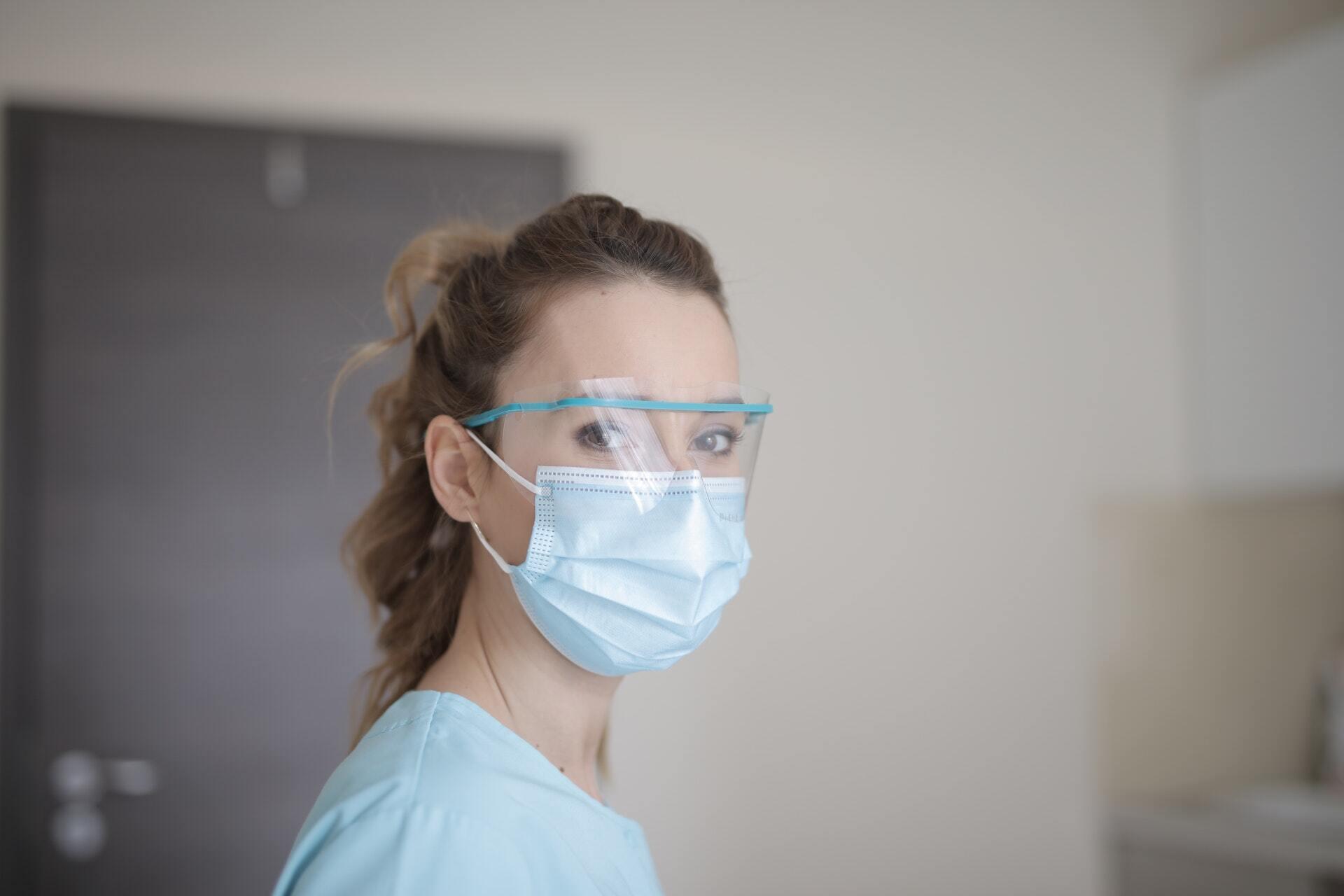 Woman nurse in blue shirt wearing face mask