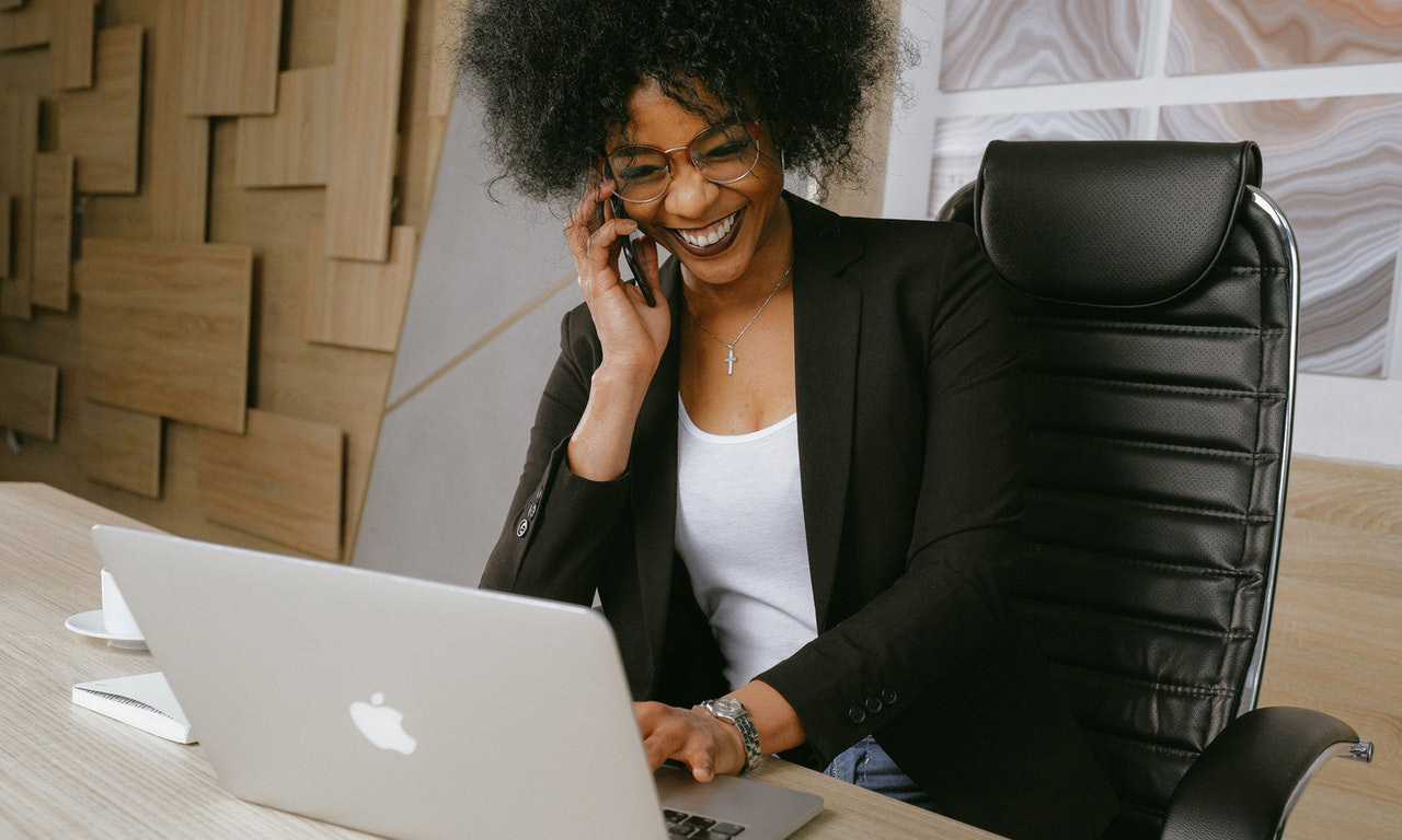 Woman smiling while on phone and computer